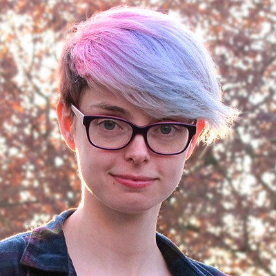 Photo of Corinne Duyvis: white woman with purple glasses and dyed blue-pink hair