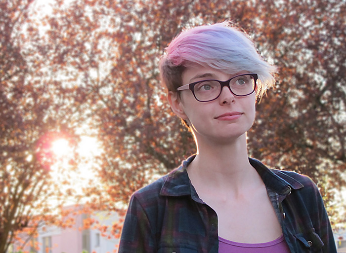 Photograph of Corinne Duyvis, a twenty-something white woman with a short pink haircut and glasses.
